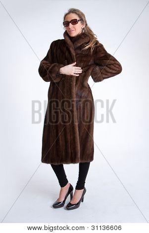 Mujer joven con abrigo de visón y gafas de sol