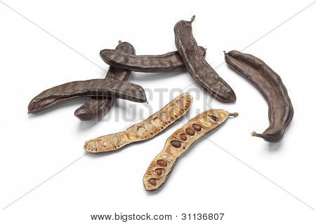Whole and half Carob pods on white background