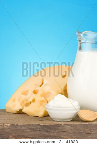 swiss cheese and milk products on wood at blue background