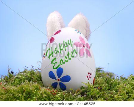 Huevo de Pascua en la hierba con bunny' oídos empujando hacia fuera desde atrás sobre cielo azul