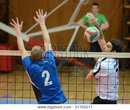 KAPOSVAR, HUNGARY - MARCH 16: Andras Geiger (R) in action at a Hungarian Championship volleyball game Kaposvar (white) vs. Kazincbarcika (blue), March 16, 2012 in Kaposvar, Hungary.