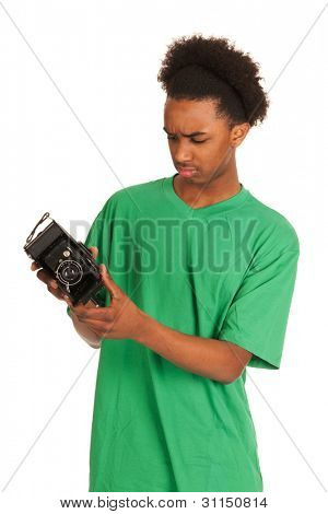 teenager boy is looking to old vintage photo camera
