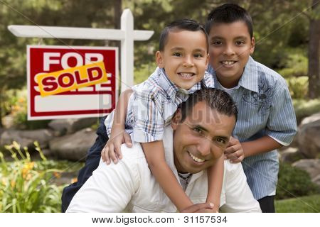 Hispanic Father and Sons in Front of a Sold Home For Sale Real Estate Sign.