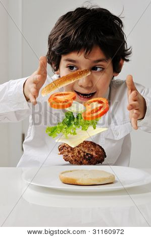 Little boy with hamburger ingredients in hands