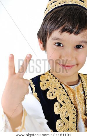 Little kid in middle-eastern clothes making peace gesture