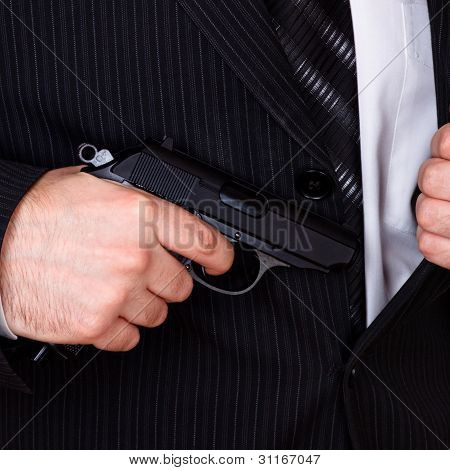 man drawing his gun from jacket pocket