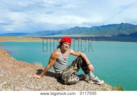 Boy Teens Sitting On  Stump By  Beautiful Lake With Green Water. Kazakhstan, Bortoguy (Series Spor