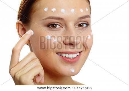 Fresh woman applying hydrating cream onto her face