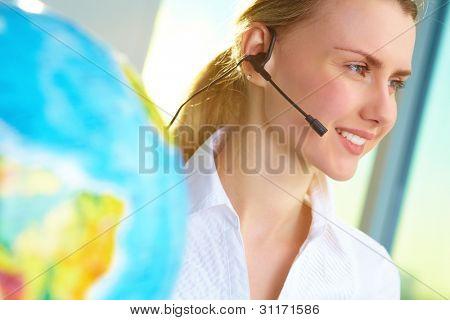 Retrato de sorridente agente de turnê com cliente de fone de ouvido de consultoria on-line