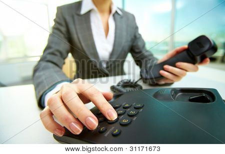 Female hand holding phone receiver and dialing number