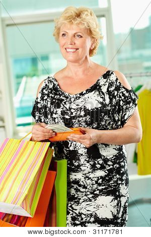 Retrato de mulher de idade média com paperbags e carteira, no departamento de vestuário