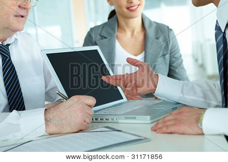 Close-up of business team of three sitting at table and planning work