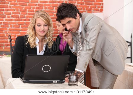 Man on a cellphone and a woman on a laptop