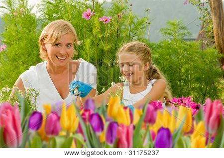 Spring garden, planting concept - mother with daughter planting flowers into the flowerpot