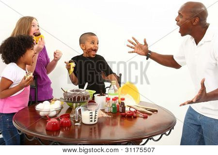 Angry dad finds kids making mess with cupcakes in the kitchen.  Interacial family over white.
