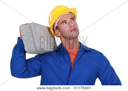 Laborer carrying cinderblock