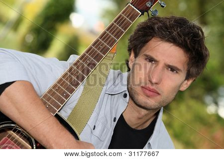 Man tightly holding his guitar