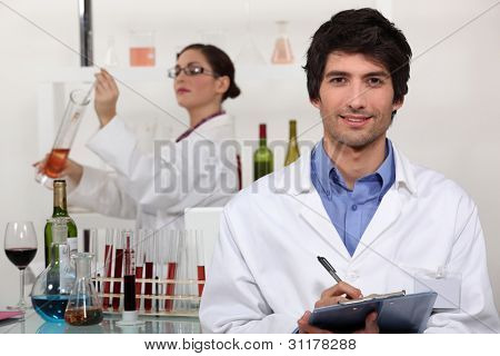 Two scientists in wine testing facility