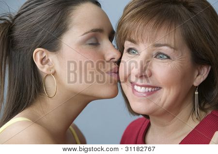 Teenage girl kissing her mother on the cheek