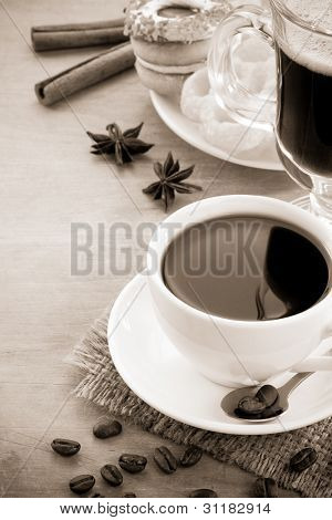 cup of coffee with beans and cakes on wood background