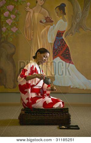 Woman in kimono pouring tea in spa room