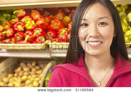 Asian woman in produce section of grocery store