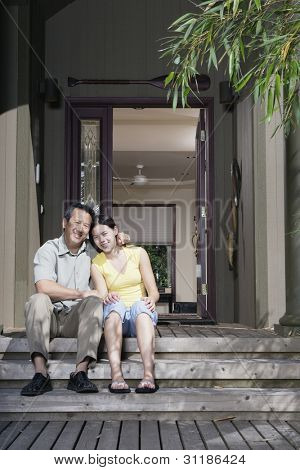 Portrait of father and daughter sitting on front steps