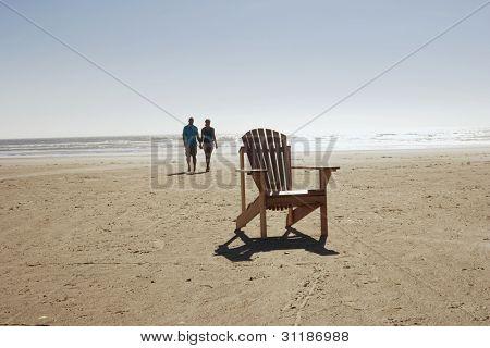 Cadeira vazia com casal caminhando na praia