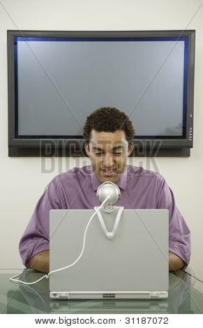 Young businessman seated behind computer