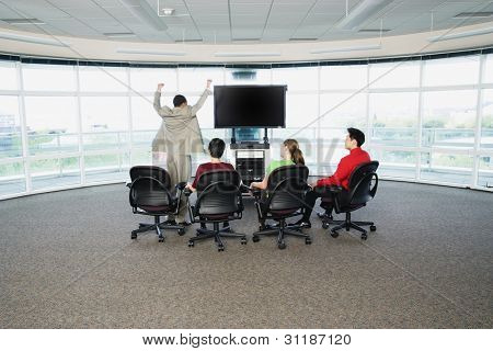 Rear view of group sitting around big screen TV with one man cheering