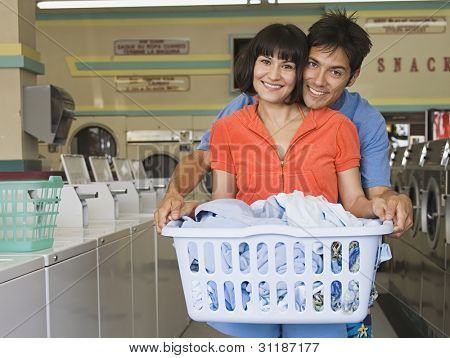 Portrait of couple with laundry hugging at laundromat