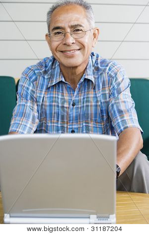 Portrait of elderly man with laptop