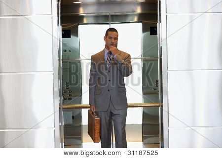 Young businessman inside elevator