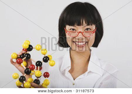 Portrait of Asian female scientist holding chemical model