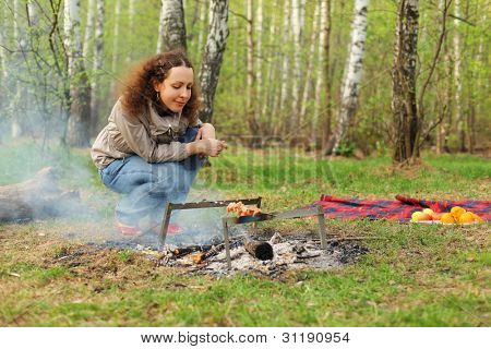 Happy woman sits near campfire with grill and barbecue in forest
