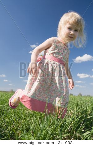 Happy Little Girl On Green Meadow