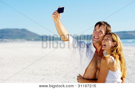 young couple pose for a self portrait at the beach, laughing and having summer fun together
