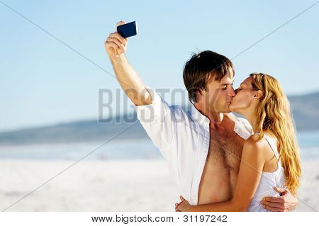 young kissing couple pose for a self portrait at the beach, laughing and having summer fun together