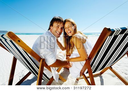 Real happy couple on a summer beach holiday pose for a portrait together, laughing and smiling with pure joy