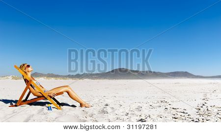 Attractive woman sunbathing alone during summer on the beach with high spf sunblock