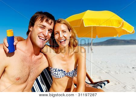 suncare couple on a summer beach vacation have good skincare with high spf sunblock