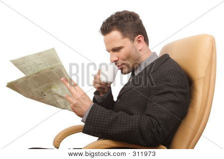 Resting Businessman Drinking Coffee And Reading Newspaper