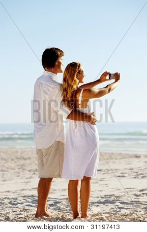 Summer beach honeymoon couple standing on the sand and taking pictures of the beautiful sunset over the ocean