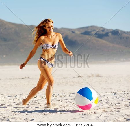 summer beach bikini girl with beachball laughing and having fun