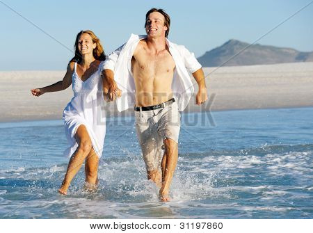 Summer beach love couple run through the shallow water splashing and having fun together. laughing and smiling carefree concept.