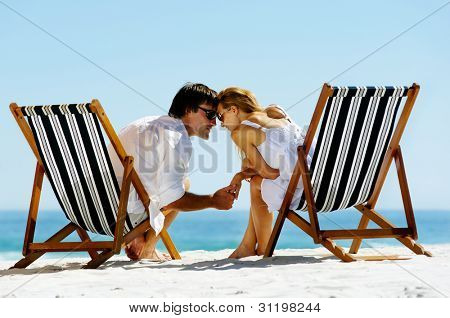young couple at the beach in summer share an intimate moment of love and affection