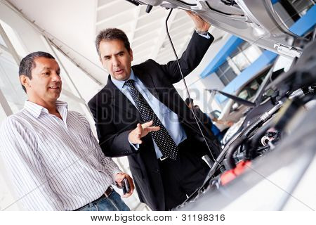 Car salesman at the dealership showing the engine to a client
