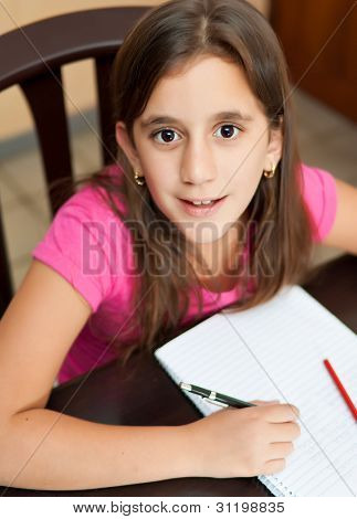 Beautiful latin girl working on her school homework and looking at the camera