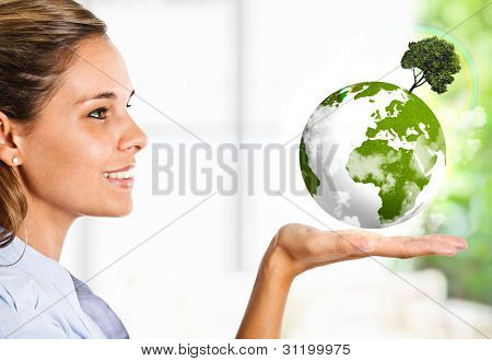 Beautiful woman looking at the earth in her hand