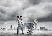 Determined Businessman Against Modern Cityscape Breaking With Violin Stone Key Figure poster